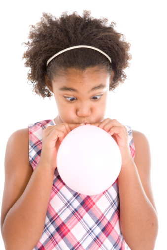 Girl blowing up a pink balloon.